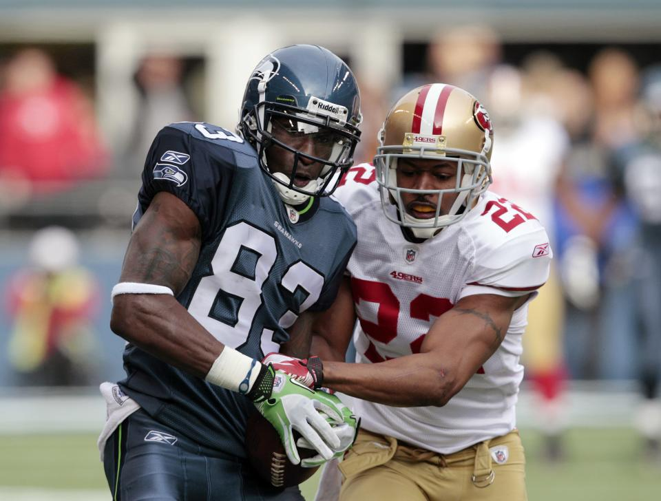 Seattle Seahawks'  Ricardo Lockette, left, fight to hold onto a 44-yard pass as San Francisco 49ers'  Carlos Rogers defends in the first half of an NFL football game Saturday, Dec. 24, 2011, in Seattle. (AP Photo/Elaine Thompson)
