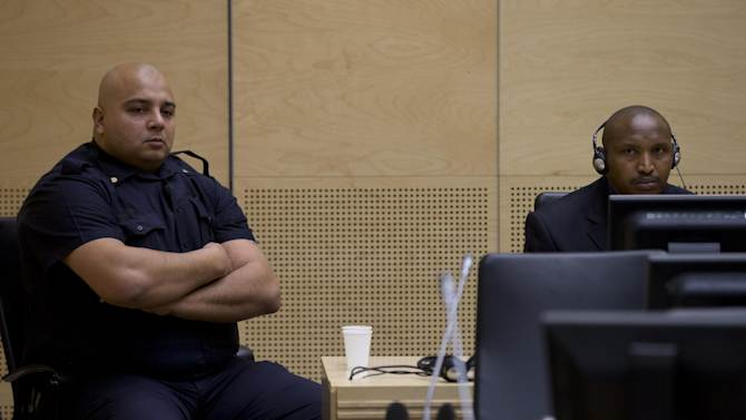 Rwandan-born warlord Bosco Ntaganda, right, is flanked by a security guard as is seen during his first appearance before judges of the International Criminal Court in The Hague, Netherlands, Tuesday March 26, 2013, since his surprise surrender to face charges including murder, rape pillaging and using child soldiers in eastern Congo. Ntaganda had been one of the court's longest-sought fugitives until he unexpectedly became the first suspect to voluntarily turn himself in by seeking refuge last week at the U.S. Embassy in the Rwandan capital, Kigali. Ntaganda allegedly led rebels who terrorized eastern Congo in brutal tribal fighting from 2002 till 2003. (AP Photo/Peter Dejong, Pool)