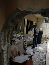 Syrians inspect the destruction at their house in the Bab Amro neighbourhood of Homs