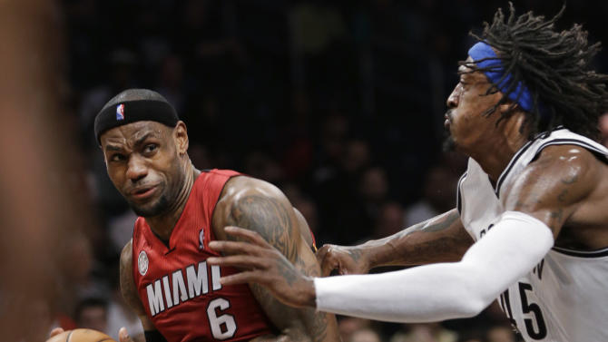 Brooklyn Nets forward Gerald Wallace defends Miami Heat forward LeBron James (6) during the first half of an NBA basketball game, Wednesday, Jan. 30, 2013, in New York. (AP Photo/Kathy Willens)