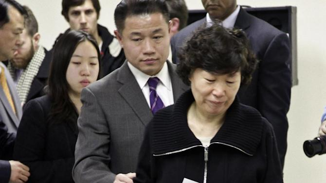 New York City Comptroller John Liu, center, escorts Serim Han, as she holds a picture of her husband Ki-Suck Han, and her daughter Ashley Han, 20, second from left, to a news conference on Wednesday, Dec. 5, 2012 in New York.   Naeem Davis, 30, was taken into custody for questioning Tuesday after security video showed a man fitting the suspect's description working with street vendors near Rockefeller Center. Police said Davis made statements implicating himself in Ki-Suck Han's death. Davis was arrested on a second-degree murder charge.  Witnesses told investigators they saw a man talking to himself Monday afternoon before he approached the 58-year-old Han of Queens at the Times Square station, got into an altercation with him and pushed him into the train's path. (AP Photo/Bebeto Matthews)