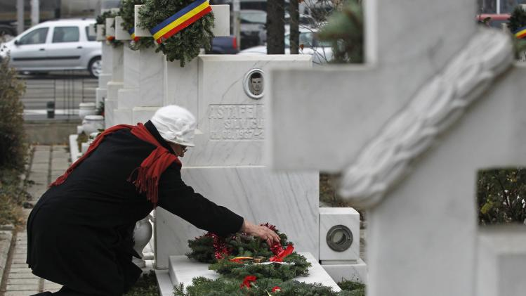A relative arranges flowers at the grave of victim during commemorations on 24th anniversary of 1989 bloody anti-communist Romanian revolution in Bucharest