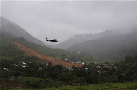 A helicopter of the federal police flies over a mudslide in the village of La Pintada, in the Mexican state of Guerrero