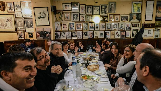 FILE - In this March 16, 2013 file photo, Turks enjoy a dinner with raki, a traditional Turkish aniseed-based alcoholic drink, at Yakup Restaurant in Istanbul, Turkey. A look at legislation passed in Turkey's parliament early Friday May 24 2013 that would ban all alcohol advertising and tighten restrictions on the sale of such beverages, and how such a law could affect tourists and liquor companies in the mainly Muslim but secular country.(AP Photo/File)