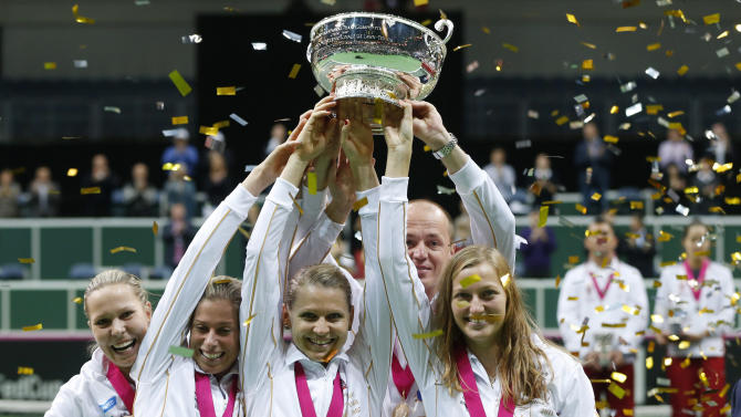 Czech Republic's team, left to right, Lucie Hradecka, Andrea Hlavackova, Lucie Safarova, Petr Pala, and Petra Kvitova celebrate with the  trophy after defeating Serbia i the final of the Fed Cup tennis tournament h in Prague, Czech Republic, Sunday, Nov. 4, 2012. (AP Photo/Petr David Josek)