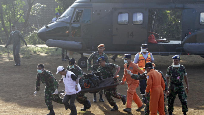 Indonesian soldiers carry a victim of  Wednesday's plane crash at Cijeruk in Bogor, West Java, Indonesia, Saturday, May 12, 2012.  Search teams who scaled a volcano's steep slopes found at least 12 bodies Friday near the wreckage of the Russian-made Sukhoi Superjet-100  that crashed in Indonesia during a demonstration flight for potential buyers, an official said. All 45 aboard the jetliner that crashed Wednesday are feared dead.(AP Photo/Achmad Ibrahim)