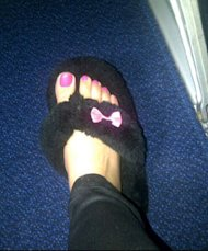 Cheryl Cole keeps her pedicure in place with fluffy slippers at the airport