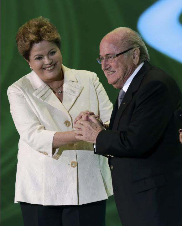 Rousseff and Blatter react on stage during the draw for the 2014 World Cup in Sao Joao da Mata