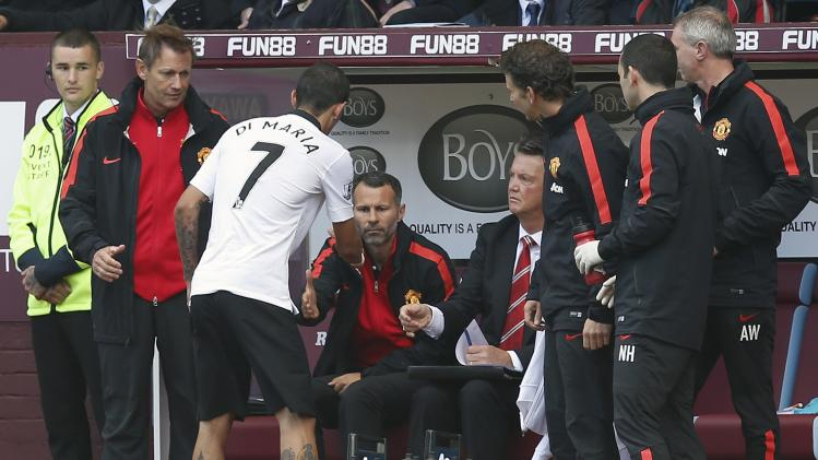 Manchester United's Di Maria shakes hands with assistant manager Giggs and manager Van Gaal after leaving the field injured during their English Premier League match against Burnley at Turf Moor in Burnley