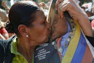 A woman kisses a portrait of Venezuelan leader Hugo Chavez during a rally outside the Miraflores Palace in Caracas, on January 10, 2013. Fighter jets streaked the sky as allies from around the region, showered praise on the cancer-stricken leader one after another and pledged their undying support