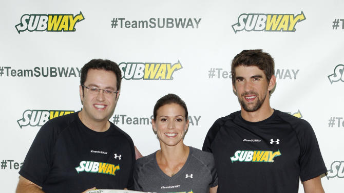 """Former Team SUBWAY marathoner Jared Fogle """"The SUBWAY Guy,"""" passes the Footlong baton to Whitney Phelps, sister of Olympic swimming champion Michael Phelps, right, as Whitney announces that she will run the ING New York City Marathon with Team SUBWAY at the Chelsea Piers Sport Center, Monday, Oct. 15, 2012 in New York. (Photo by Jason DeCrow/Invision for SUBWAY/AP Images)"""