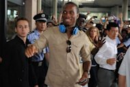 Ivory Coast striker Didier Drogba (C) exits Pudong international airport after arriving in Shanghai on July 14. Drogba was given a hero&#39;s welcome as he arrived in China Saturday to start a two-and-a-half year contract that is expected to make him one of football&#39;s highest-paid players