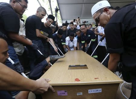 The coffin of MH17 First Officer Hakimi Hanapi is lowered during his burial in Putrajaya