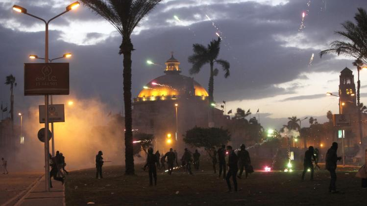 Cairo University students, supporters of the Muslim Brotherhood and ousted Egyptian President Mursi, throw fireworks towards security forces during a clash in Cairo