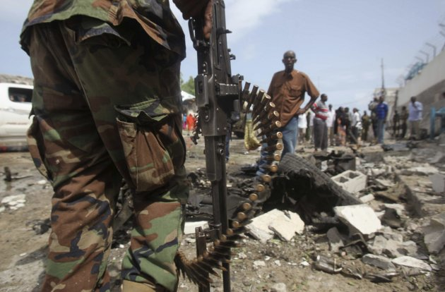 Somali government soldiers stand at scene of a suicide bomb attack outside the United Nations compound in the capital Mogadishu