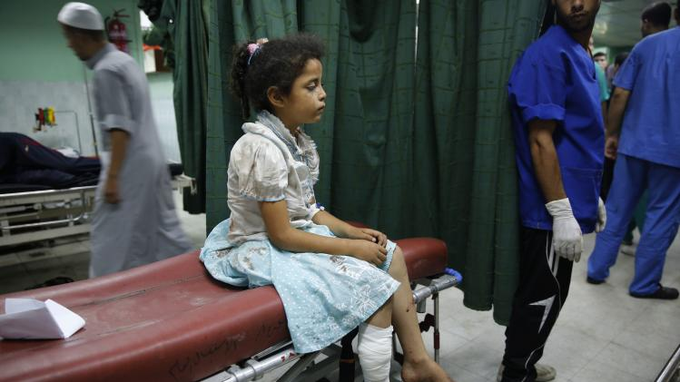 An injured Palestinian girl sits at a hospital in the northern Gaza Strip