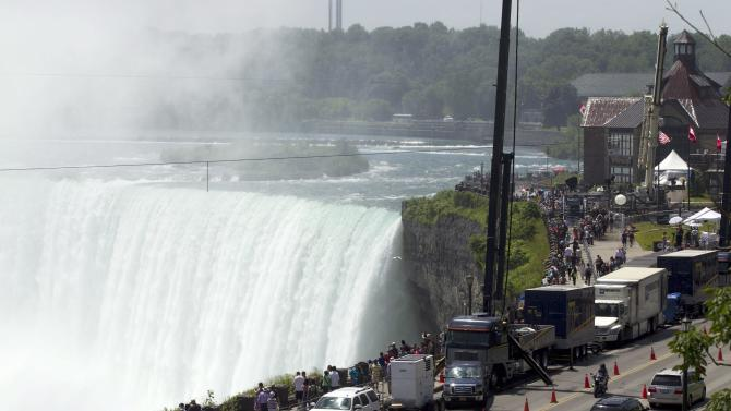 Spectators and media gather to see the 550 metre-long tightrope that Nik Wallenda will use hangs over Niagara Falls in Niagara Falls, Ontario, Canada., on Friday, June 15, 2012.  Conditions appear good leading up to the nationally televised stunt scheduled for Friday night. When Wallenda leaves terra firm about 10:15, it should be in the low 60s with winds under 10 mph from the east, roughly at his back.  (AP Photo/The Canadian Press, Frank Gunn)