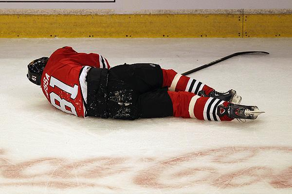 Chicago Blackhawks' Marian Hossa lies on the ice after being checked in the head by Phoenix Coyotes' Raffi Torres