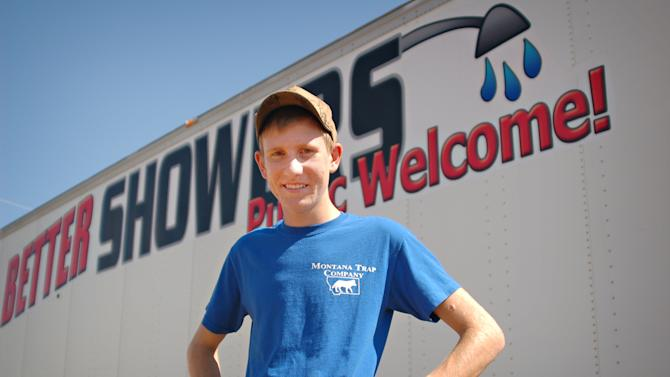 In this Thursday, Aug. 23, 2012 photo, Evan Jensen stands beside his mobile shower business, Better Showers, near Alexander, N.D. Jensen raised money for the facility, which caters largely to workers in North Dakota's oil patch, by trapping muskrats and hopes profits from the business will pay for his college tuition. (AP Photo/James MacPherson)