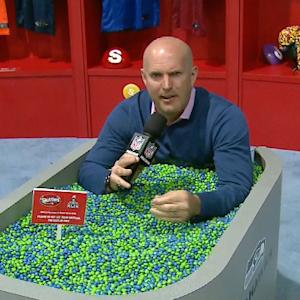NFL Media's Adam Rank sits in a tub of Skittles
