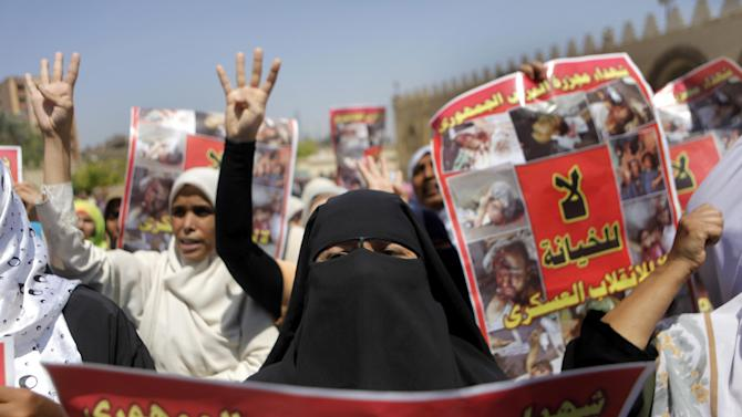 """Supporters of Egypt's ousted President Mohammed Morsi hold posters showing victims of a military crackdown on their protest camp during a march in Cairo, Friday, Aug. 23, 2013. Arabic reads, """"no for treachery"""", """"no for military coup"""" and """"martyrs of republican guard massacre ."""" Egyptian security and military forces deployed Friday around Cairo, closing off traffic in some major thoroughfares and in the city center ahead of protests by supporters of ousted President Mohammed Morsi. (AP Photo/Amr Nabil)"""