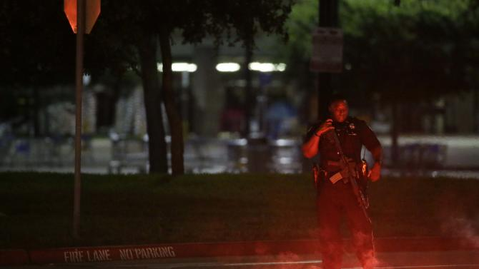 An armed police officer stands guard at a parking lot near the Curtis Culwell Center where a provocative contest for cartoon depictions of the Prophet Muhammad was held Sunday, May 3, 2015, in Garland, Texas. The contest was put on lockdown Sunday night and attendees were being evacuated after authorities reported a shooting outside the building. (AP Photo/LM Otero)
