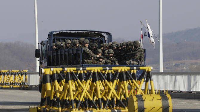 South Korean army soldiers on the truck pass at barricaded Unification Bridge near the border village of Panmunjom, that has separated the two Koreas since the Korean War, in Paju, north of Seoul, South Korea, Wednesday, April 10, 2013. A few hundred South Korean managers, some wandering among quiet assembly lines, were all that remained Tuesday at the massive industrial park run by the rival Koreas after North Korea pulled its more than 50,000 workers from the complex. Other managers stuffed their cars full of finished goods before heading south across the Demilitarized Zone that divides the nations. (AP Photo/Lee Jin-man)