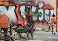 A construction worker works pushes a wheelbarrow in Bucharest on August 10. The recovery in Romania&#39;s economy after two years of severe recession is now coming under threat, analysts warn, victim to the months-long political crisis that has engulfed the EU country
