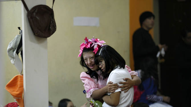 "In this Sept. 21, 2012 photo, two actresses embrace in a backstage dressing room prior to their performance in ""Suenos,"" or ""Dreams,"" one of Ecuador's most successful musicals, at the Casa de la Cultura theater in Quito, Ecuador. The musical is based in part on the dreams of young people with disabilities and is presented by the nonprofit foundation El Triangulo. (AP Photo/Dolores Ochoa)"
