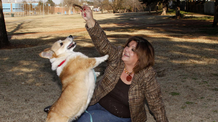 Cara Maschmeier, who serves as secretary on the Singles in Agriculture national board, plays with her 4-year old Pembroke Welsh Corgi, Carson, in an Oklahoma City park, Wednesday, March 27, 2013. (AP Photo/Sue Ogrocki)