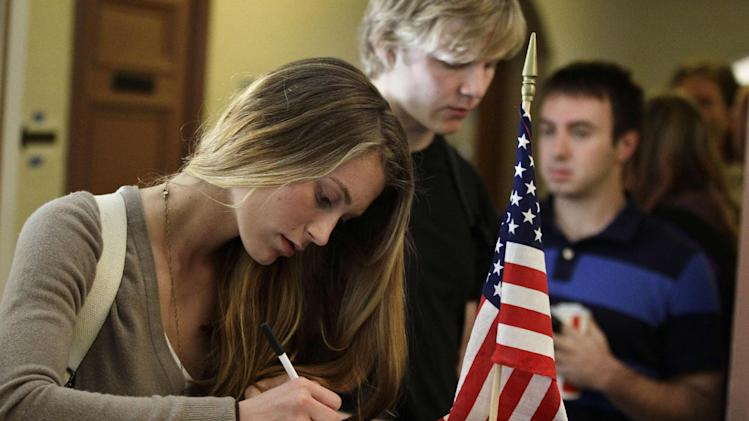 FILE - In this Nov. 6, 2012 file photo, Madeline Nicole Kreyger, from Santa Barbara, Calif., casts her vote at a polling station on the campus of the University of Colorado in Boulder, Colo. As a divisive legislative session ended this month, Colorado Democrats muscled through the Statehouse a massive elections reform bill that allows voters to register up until Election Day and still cast their ballots. It's the latest _ and most substantial _ development in a nationwide Democratic Party effort to strike back at two years of Republican success in passing measures to require identification at polling places and purge rolls of suspect voters.  (AP Photo/Brennan Linsley, File)