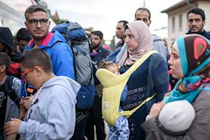Migrants board a train to Graz at a railway station…