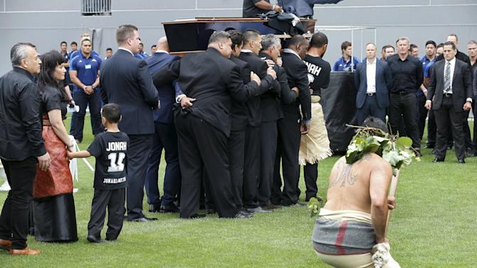 Former and present All Black's (R) watch as former All Black Jonah Lomu's casket is carried out of Eden Park, followed by his widow Nadene and children, during his memorial service in Auckland