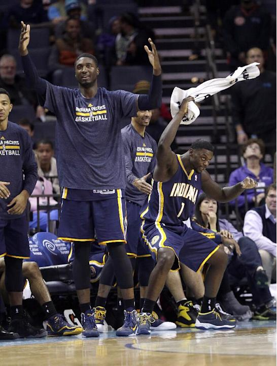 Indiana Pacers' Roy Hibbert, left, and Lance Stephenson, right, celebrate as a teammate makes a basket against the Charlotte Bobcats during the second half of an NBA basketball game in Charlotte, N.C.