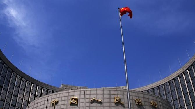 A Chinese national flag flutters in front of the headquarters of the People's Bank of China, China's central bank, in central Beijing