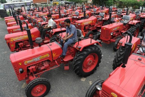 <p>Indian workers inspect new tractors for sale at a Mahindra dealership for agricultural vehicles in Sanand town, some 30 kms from Ahmedabad, in August 2012. Mahindra announced Tuesday it was opening a technical center near Detroit to supply engineering services to the huge US car industry.</p>