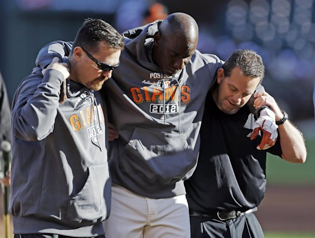 San Francisco Giants first base coach Roberto Kelly is helped off the field after getting hit with a ball during a practice session for baseball's National League championship series Saturday, Oct. 13, 2012, in San Francisco. The Cardinals play the San Francisco Giants in Game 1 of the NLCS on Sunday. (AP Photo/Mark Humphrey)