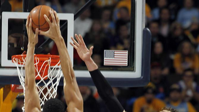Denver Nuggets center JaVale McGee (34) dunks between Los Angeles Lakers center Dwight Howard (12) and forward Pau Gasol (16), of Spain, in the first quarter of an NBA basketball game in Denver, Wednesday, Dec. 26, 2012. (AP Photo/David Zalubowski)