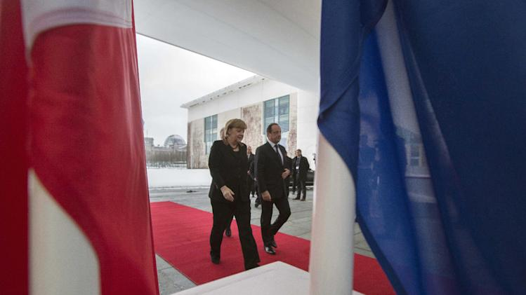 German Chancellor Angela Merkel, left, accompanies French President Francois Hollande, right, into the Chancellery in Berlin, Germany, Tuesday, Jan. 22, 2013. France and Germany mark 50 years since they signed the Elysee Treaty, the post-war friendship pact between the former enemies. (AP Photo/Gero Breloer)