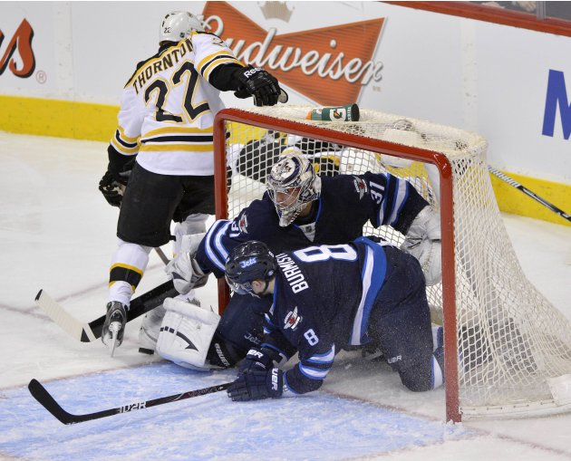 Jets' Burmistrov slides into the net after goaltender Pavelec made a save against Bruins' Thornton during their NHL hockey game in Winnipeg