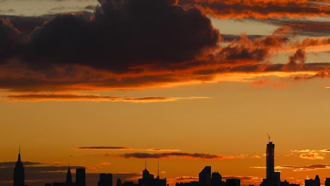 The sun sets behind the New York skyline as fans wait for the start of a baseball game between the New York Mets and the Miami Marlins Tuesday, Sept. 16, 2014, in New York. (AP Photo/Frank Franklin II)
