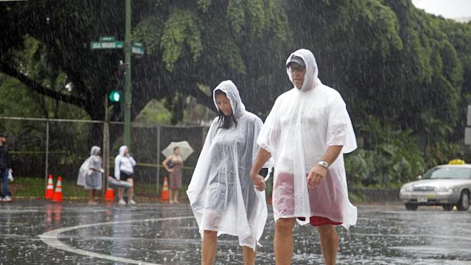 Tourists cope wet weather in Waikiki in Honolulu Sunday, Oct. 19, 2014. Hurricane Ana brought a steady rain to the Hawaiian Island of Oahu as it passed about 180 miles west. (AP Photo/P. Solomon Banda)