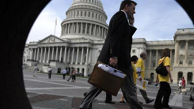 People walk past the U.S. Capitol, seen through a porthole in nearby brickwork, in Washington, October 3, 2013.