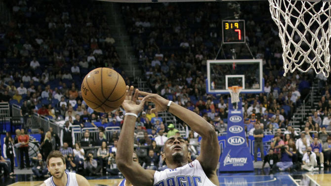 Orlando Magic's Arron Afflalo (4) loses control of the ball as he collides with New York Knicks' Tyson Chandler, lower left, during the first half of an NBA basketball game, Tuesday, Nov. 13, 2012, in Orlando, Fla. (AP Photo/John Raoux)