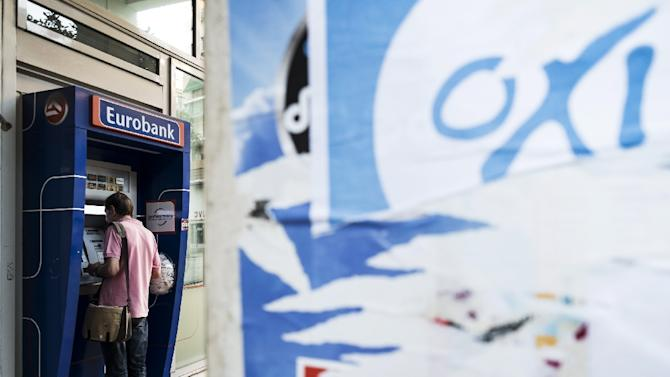 A man withdraws money from an ATM in downtown Athens on July 4, 2015