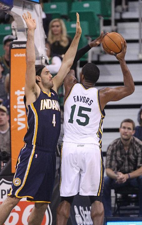Utah Jazz's Derrick Favors (15) shoots as Indiana Pacers' Luis Scola (4) defends in the first half during an NBA basketball game Wednesday, Dec. 4, 2013, in Salt Lake City
