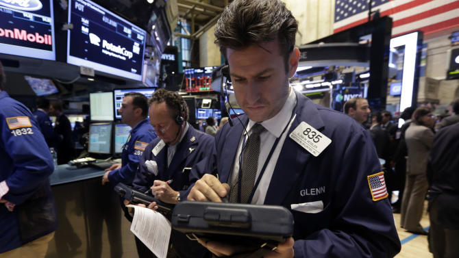 Trader Glenn Kessler, center, works on the floor of the New York Stock Exchange Friday, Dec. 6, 2013. The stock market is up sharply after the U.S. government reported a big increase in hiring last month. (AP Photo/Richard Drew)