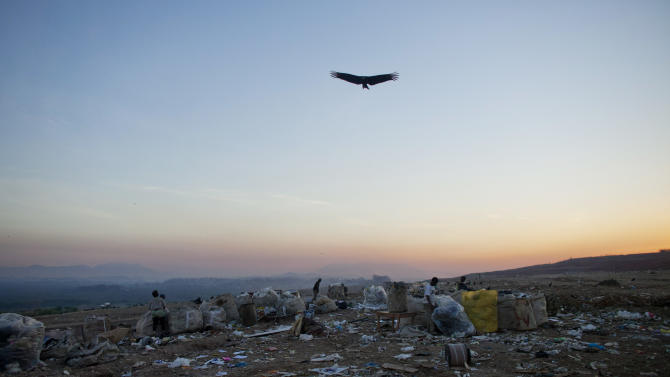 In this May 29, 2012 photo, a vulture flies over Jardim Gramacho, one of the world's largest open-air landfills, in Rio de Janeiro, Brazil. Jardim Gramacho, a vast, seaside mountain of trash where thousands of people made a living sorting through the debris by hand, is closing after three decades in service. (AP Photo/Victor R. Caivano)