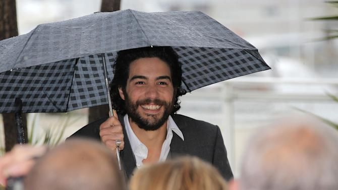 Actor Tahar Rahim arrives under his umbrella  during a photo call for the film Grand Central at the 66th international film festival, in Cannes, southern France, Saturday, May 18, 2013. (AP Photo/Lionel Cironneau)