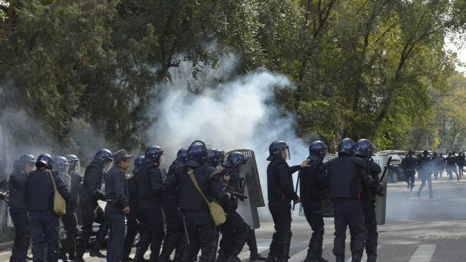 Police officers use tear gas trying to stop protesters in downtown Bishkek, Kyrgyz capital on Wednesday, Oct. 3, 2012. Around 1,000 people gathered in the center of the city for a rally, organized by nationalist politicians Sapar Zhaparov and Kamchibek Tashiyev, ostensibly to demand the nationalization of a controversial gold mine in the east of the Central Asian nation. Police officers protecting the government building, known as the White House, used dogs and smoke bombs to disperse a group of young men who attempted to scale the gates.  (AP Photo/ Vladimir Voronin)